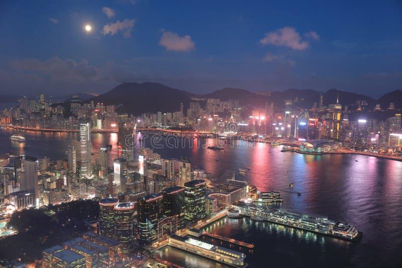 un horizonte de Hong Kong en la noche con la luna fotos de archivo libres de regalías