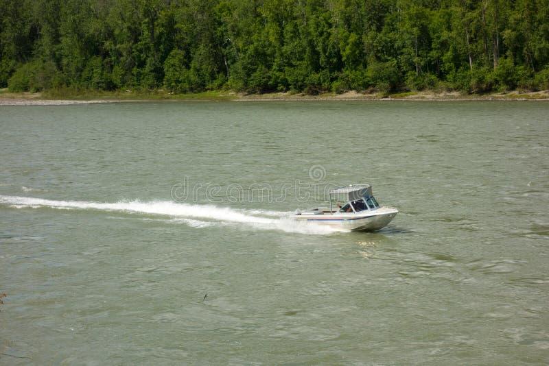 Un hors-bord voyageant en amont contre un courant fort pendant le printemps photos stock