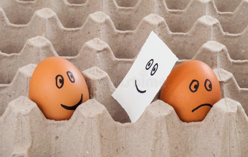 Un huevo marrón del pollo con la demostración triste de la cara a otra cara de la sonrisa de la falsificación del huevo en etique fotografía de archivo libre de regalías