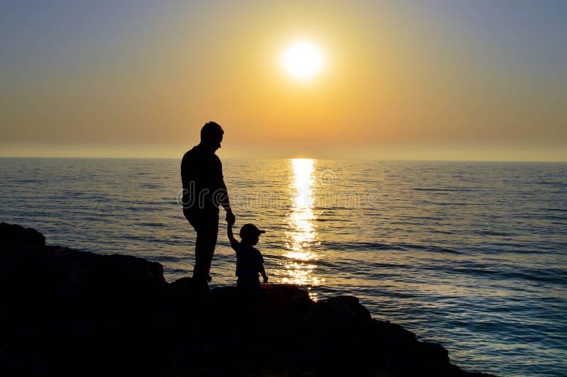 Un humain tient un enfant par la main et ils observent le coucher du soleil ensemble photos libres de droits