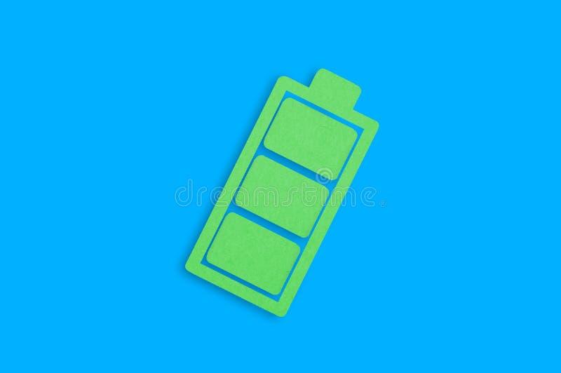 Un icono de papel hecho a mano de batería llena en el centro de tabla azul Visión superior ilustración del vector