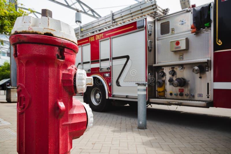 Un idrante antincendio rosso davanti ad un grande camion dei vigili del fuoco rosso con impianto idraulico per i collegamenti del fotografie stock