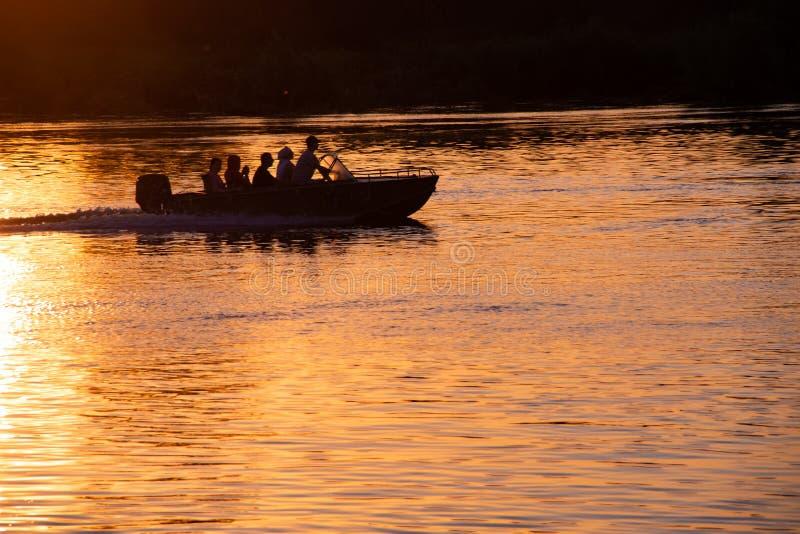 Un'imbarcazione a motore naviga sul fiume al tramonto fotografia stock libera da diritti