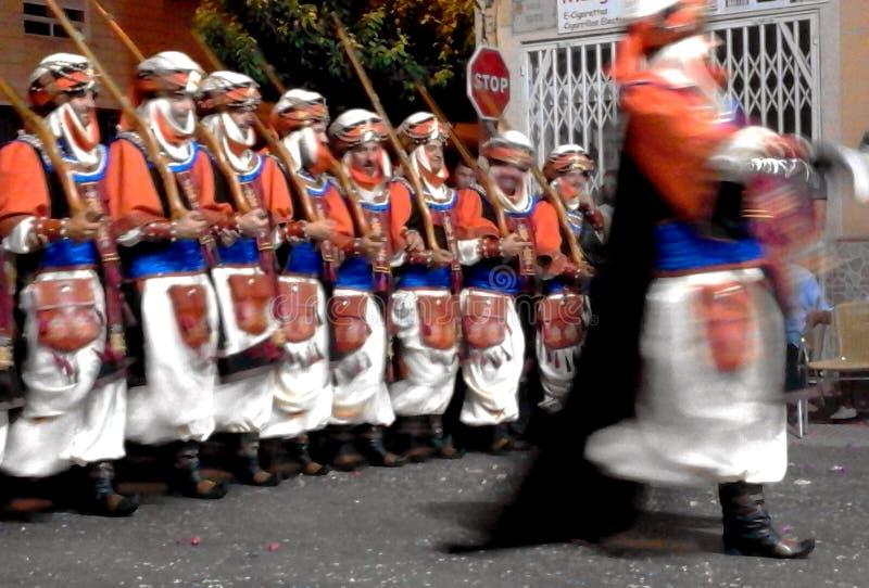 Un'immagine astratta di un gruppo di partecipanti ad un festival locale tradizionale delle parate della gente costumed dei musulm fotografia stock