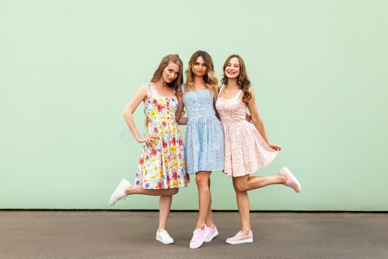 Un'immagine completa di altezza di tre ragazze insolenti felici, migliori amici divertendosi, ridenti sul fondo verde fotografia stock
