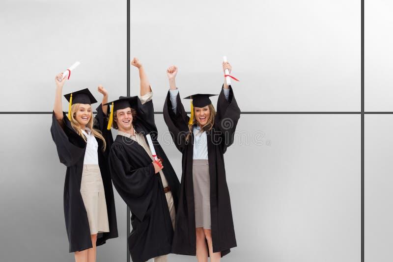 Un'immagine composita di tre studenti in abito laureato che alza le loro armi immagini stock libere da diritti