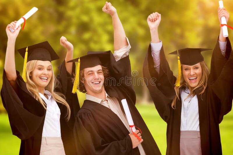 Un'immagine composita di tre studenti in abito laureato che alza le loro armi immagine stock