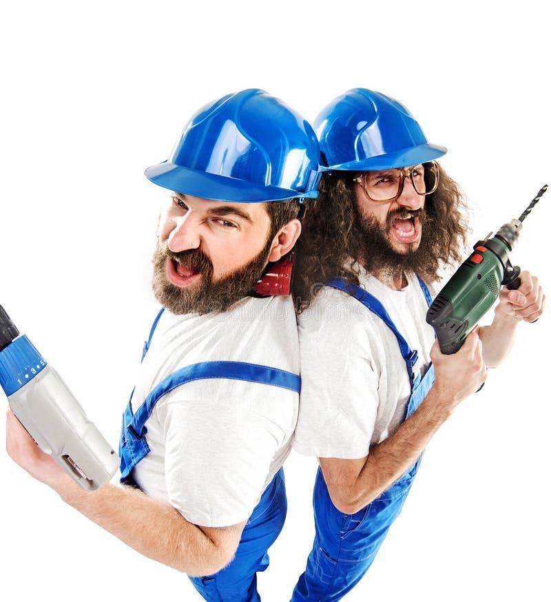 Un'immagine concettuale di due costruttori mentre lavorando immagini stock libere da diritti