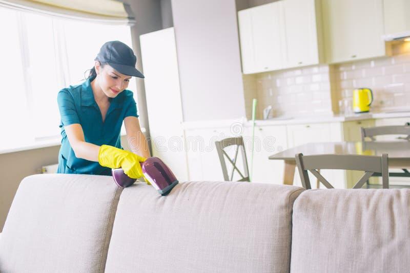 Un'immagine del bordo di pulizia della ragazza del sofà Usa il piccolo aspirapolvere La donna è professionale Lavora perfettament immagini stock