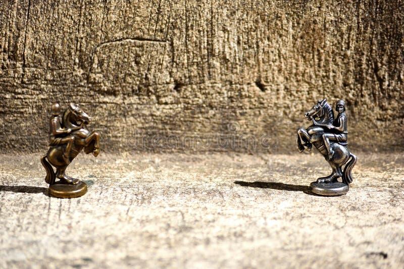 Un'immagine del primo piano di due pezzi degli scacchi bronzei dei cavalieri dei pezzi degli scacchi messi accanto ad affrontarsi fotografia stock libera da diritti