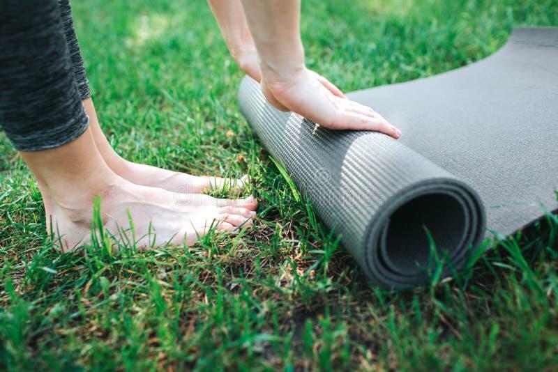 Un'immagine delle gambe e delle mani femminili del ` s La ragazza sta rotolando sul carimate Fine in su Yoga e concetto di Pilate fotografia stock libera da diritti