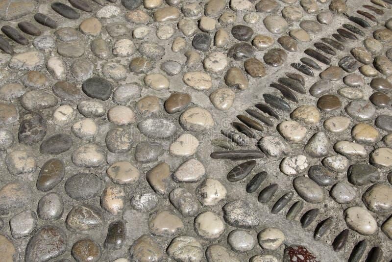 Un'immagine delle mattonelle d'annata della pavimentazione del ciottolo del fondo piacevole della pietra immagine stock