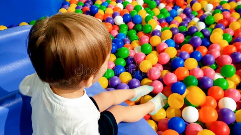 Un'immagine di 3 anni del ragazzo del bambino che gioca e che si diverte sul campo da giuoco con i lotti di piccola palla variopi fotografie stock