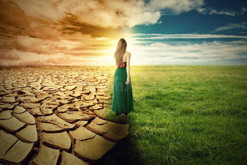 Un'immagine di concetto del mutamento climatico Erba verde del paesaggio e terra di siccità fotografia stock libera da diritti