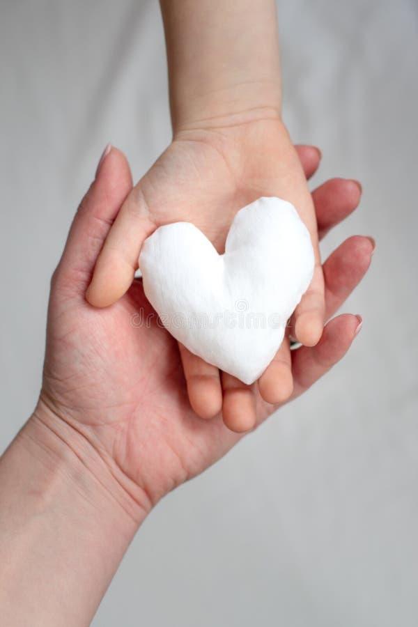 Un'immagine di due mani che tengono il cuore bianco del tessuto Madre e bambino insieme immagini stock libere da diritti