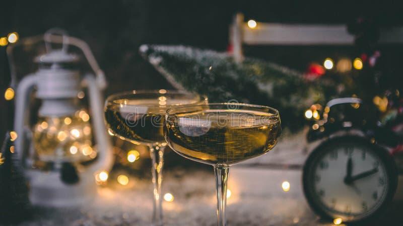 Un'immagine di due vetri del champagne su fondo vago con l'albero di Natale, lanterna, orologio fotografie stock