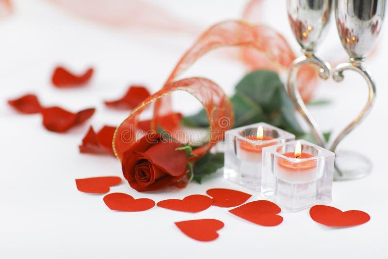 Un'immagine di sfondo di due candele e di bella rosa su un bianco immagine stock