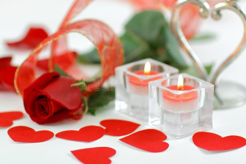 Un'immagine di sfondo di due candele e di un bello è aumentato su un fondo bianco fotografia stock libera da diritti