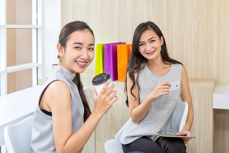 Un'immagine di una ragazza sorridente che paga con una carta di credito e un telefono cellulare nell'acquisto online immagine stock