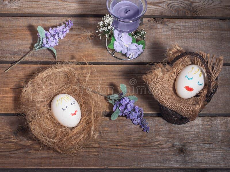 Un'immagine divertente per Pasqua, due uova con i fronti dipinti Canestro e paglia su cui sonno delle uova immagini stock
