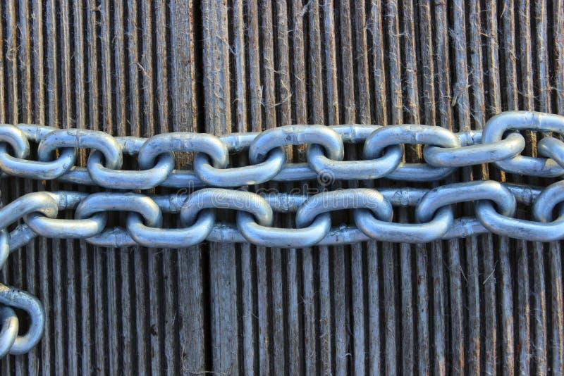 Un'immagine potata del primo piano di una catena a maglia Catena del metallo sopra fondo di legno immagine stock libera da diritti