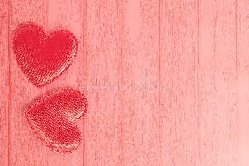 Un'immagine rosa pastello di due cuori del biglietto di S. Valentino su un fondo di legno della plancia Amore di concetto, giorno immagine stock