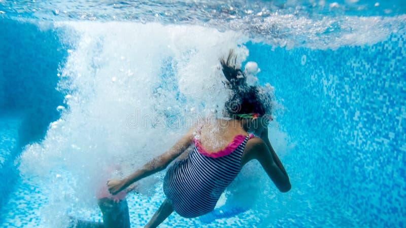 Un'immagine subacquea dell'adolescente due che salta e che si tuffa piscina alla palestra fotografia stock libera da diritti
