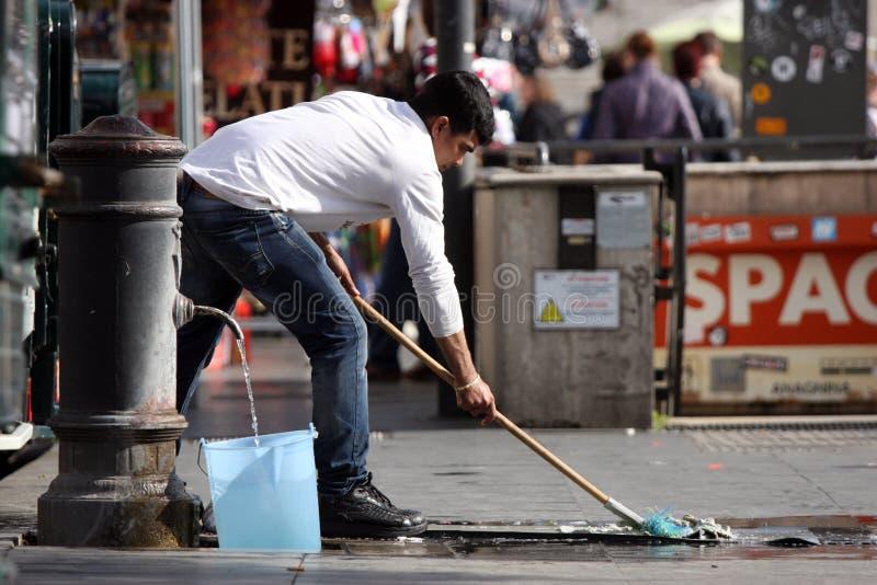 Un immigrato pulisce la strada immagini stock