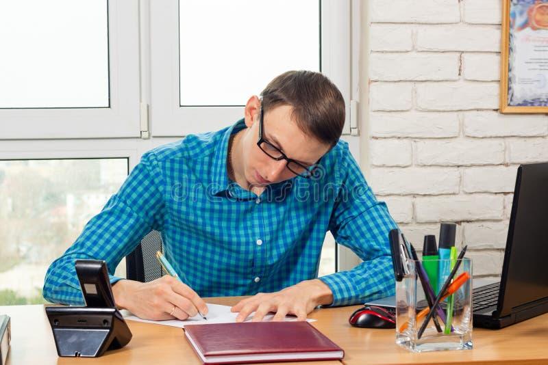 Un impiegato di concetto redige una dichiarazione alla tavola fotografia stock libera da diritti