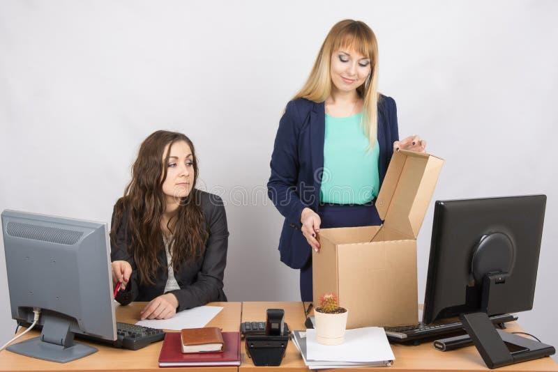 Un impiegato nell'ufficio che guarda un nuovo collega che sistema le cose fotografie stock libere da diritti