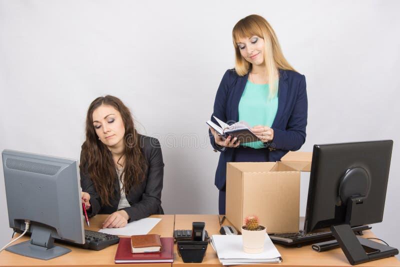 Un impiegato nell'ufficio presenta felicemente le cose circa i colleghi immagini stock libere da diritti