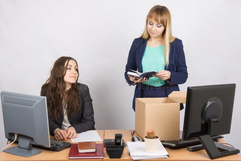 Un impiegato nell'ufficio sistema felicemente le cose intorno, guardando i suoi colleghi fotografie stock