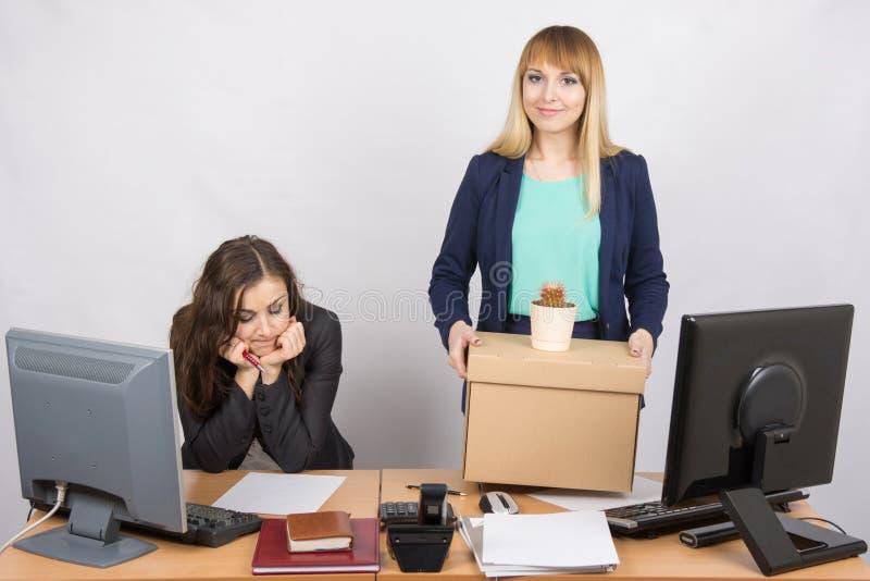 Un impiegato nell'ufficio tiene felicemente il collega triste vicino di cose fotografie stock libere da diritti
