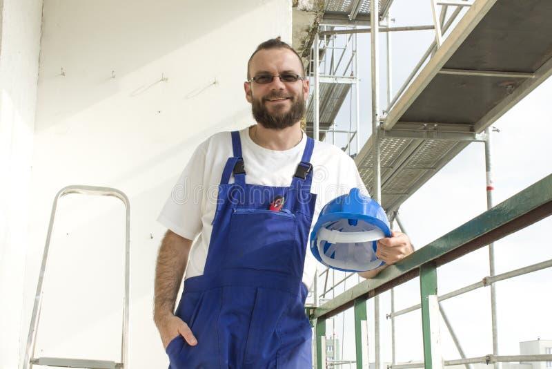 Un impiegato in un'attrezzatura del lavoro su un cantiere Impianti ad altitudine fotografia stock