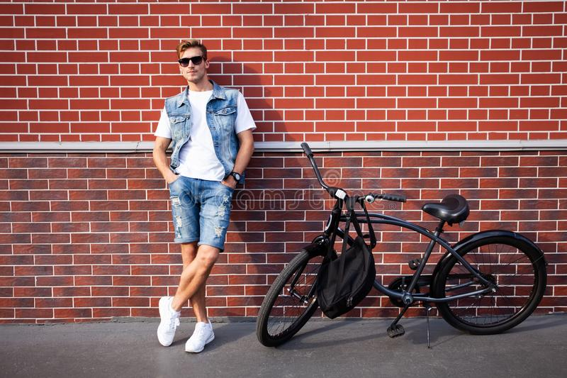 Un inconformista elegante joven que presenta al lado de su bicicleta imagen de archivo libre de regalías