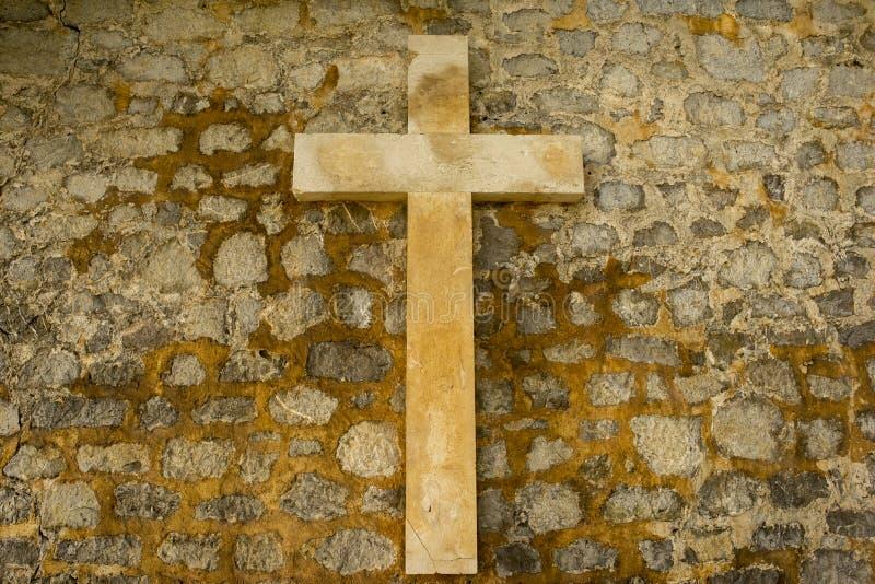 Un incrocio cristiano su una parete di pietra fotografia stock libera da diritti