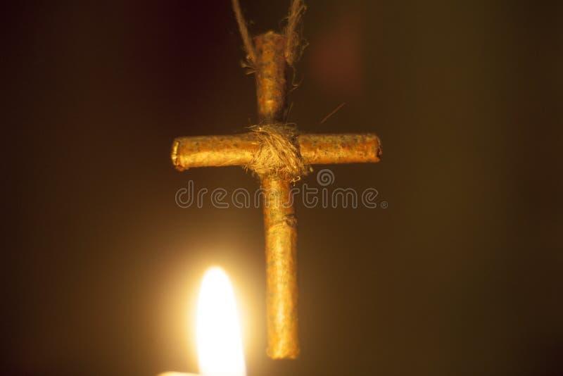 Un incrocio di legno contro le fiamme della candela immagini stock libere da diritti