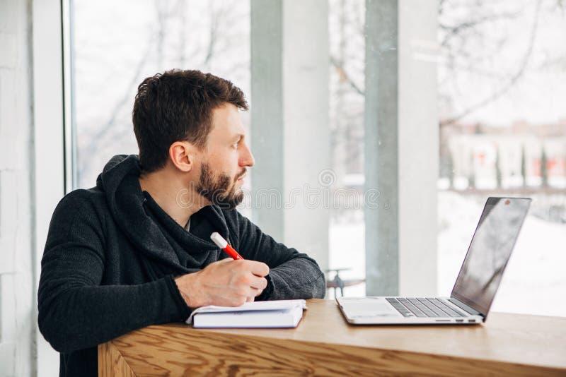 Un indépendant écrit une note dans un carnet et regarde la fenêtre images stock