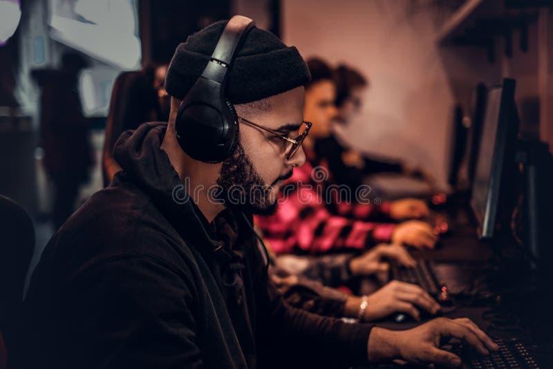 Un individuo afroamericano joven, gozando pasando tiempo con sus amigos, jugando en un videojuego multijugador en una PC en a imágenes de archivo libres de regalías