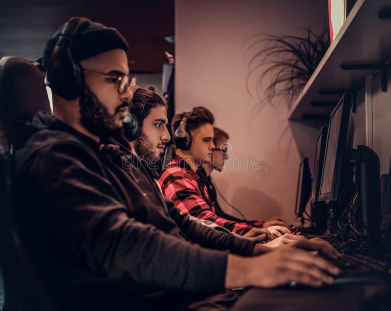 Un individuo afroamericano joven, gozando pasando tiempo con sus amigos, jugando en un videojuego multijugador en una PC en a foto de archivo
