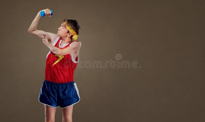 Un individuo anormal divertido, fino en ropa de deportes con las pesas de gimnasia que muestran musles imágenes de archivo libres de regalías