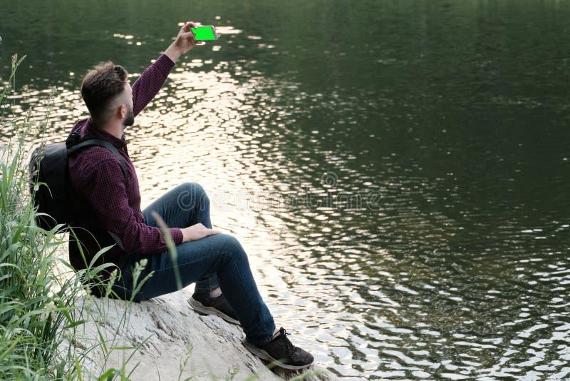 Un individuo barbudo con un teléfono en sus manos se sienta en una piedra por el río El viajero con una mochila y un smartphone h fotografía de archivo