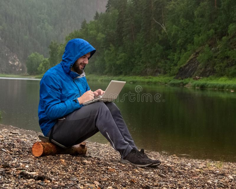 Un individuo barbudo contento en una chaqueta azul con una capilla se sienta en el banco de un río bajo la lluvia con un ordenado foto de archivo