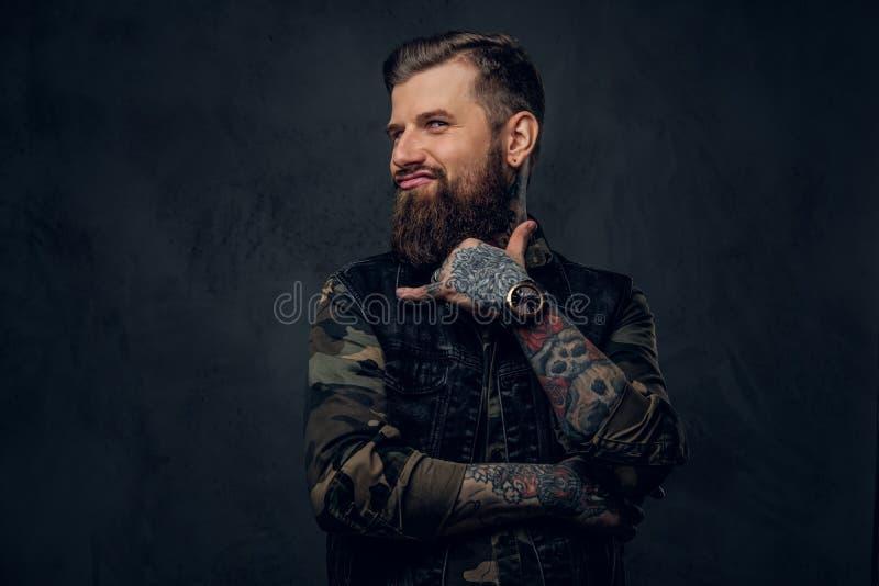 Un individuo barbudo divertido con las manos tatuadas que muestran la muestra del shaka y que miran una cámara Foto del estudio c imagen de archivo libre de regalías
