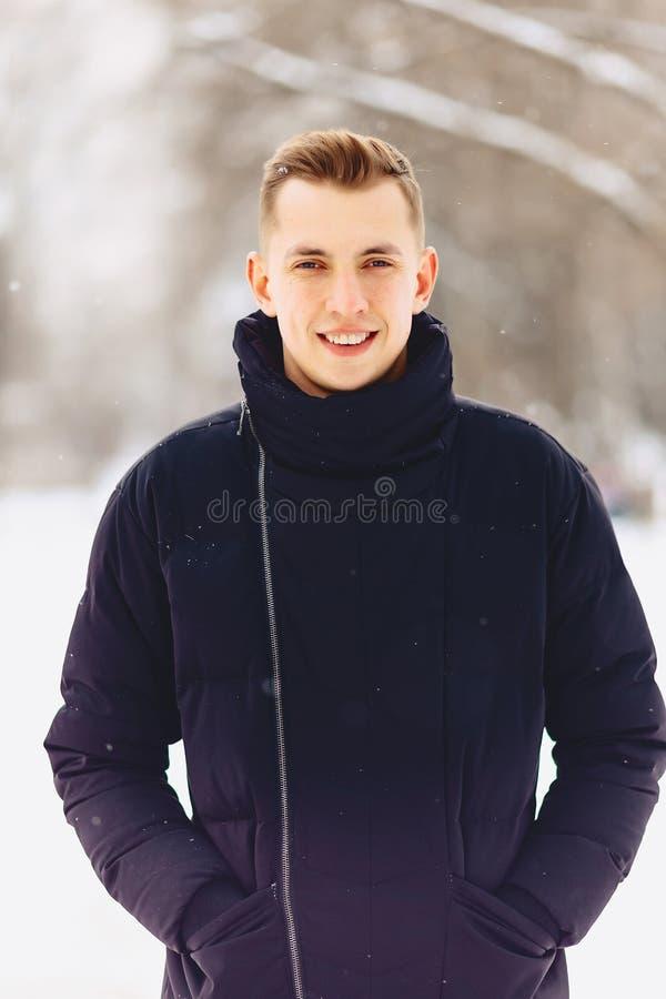 Un individuo con el pelo corto ligero en actitudes de una chaqueta del invierno a vino imágenes de archivo libres de regalías