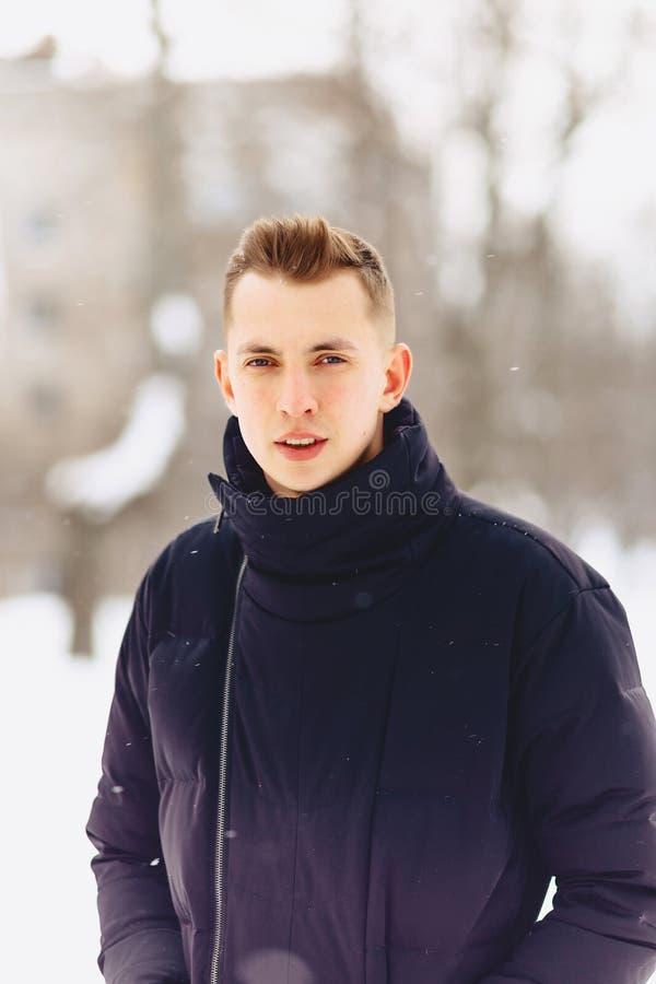 Un individuo con el pelo corto ligero en actitudes de una chaqueta del invierno a vino fotos de archivo