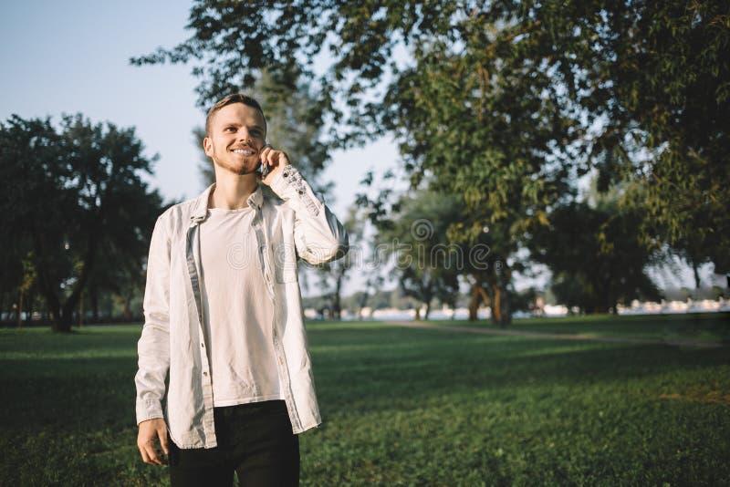 Un individuo con un teléfono en parque fotografía de archivo libre de regalías