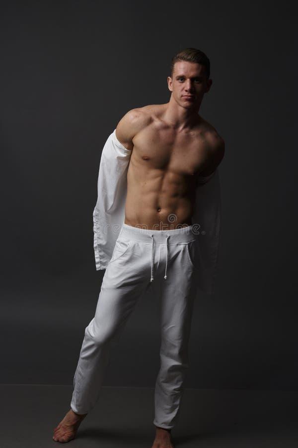 un individuo con un torso desnudo, en los pantalones blancos, y en una camisa blanca, se coloca en un fondo gris foto de archivo