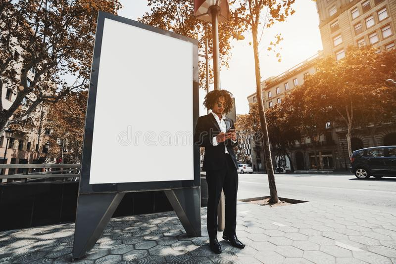 Un individuo de lujo con el teléfono móvil cerca de la maqueta de la bandera de la información fotos de archivo