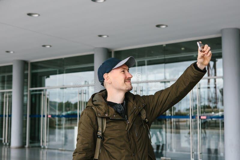 Un individuo en una gorra de béisbol o un turista fotografía o hace el selfie en el teléfono imagenes de archivo